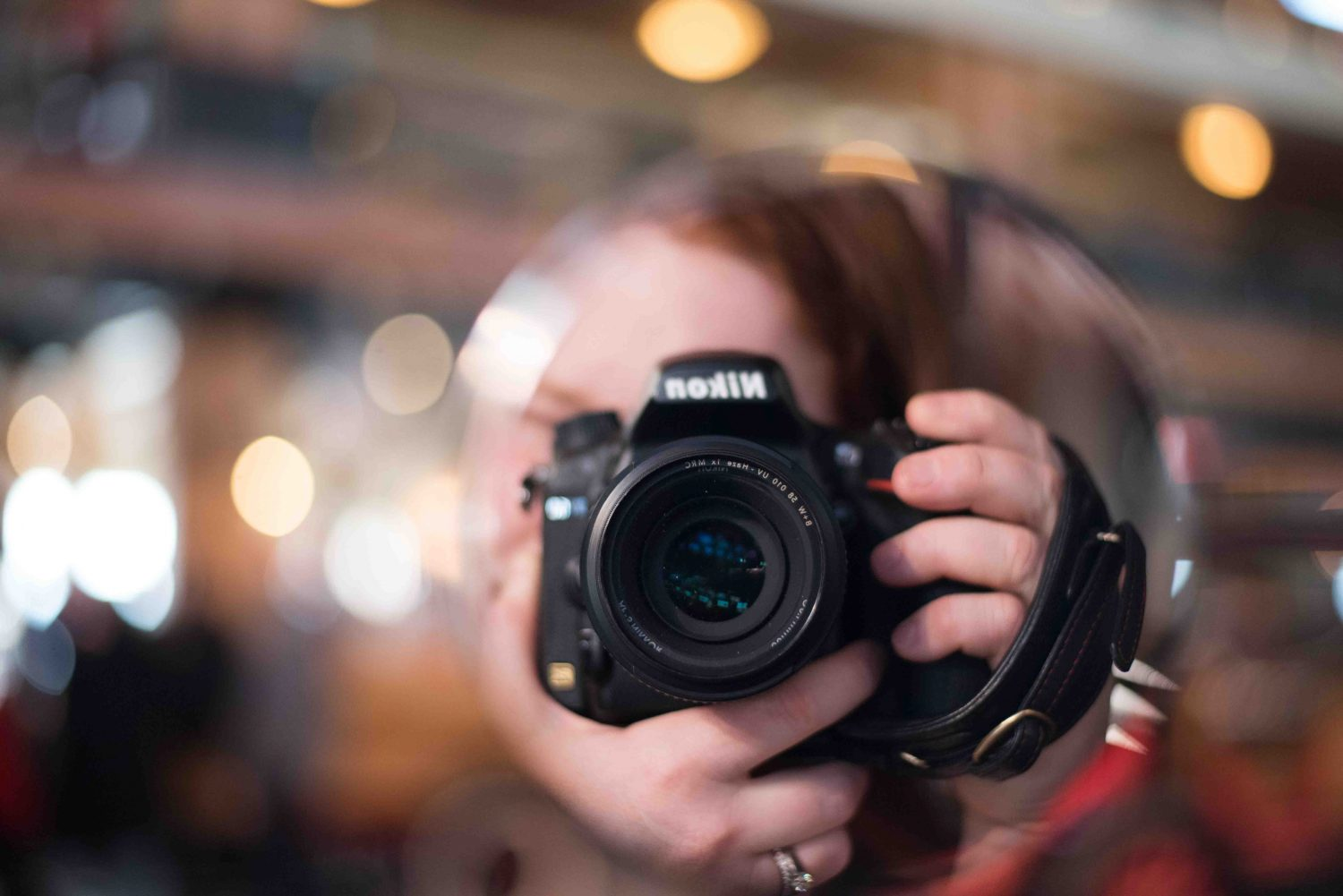Reflected image of woman taking a photograph holding Nikon camera with blurry background