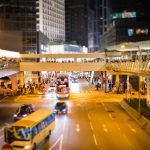 Tilt shift of busy street at night with overhead footbridges