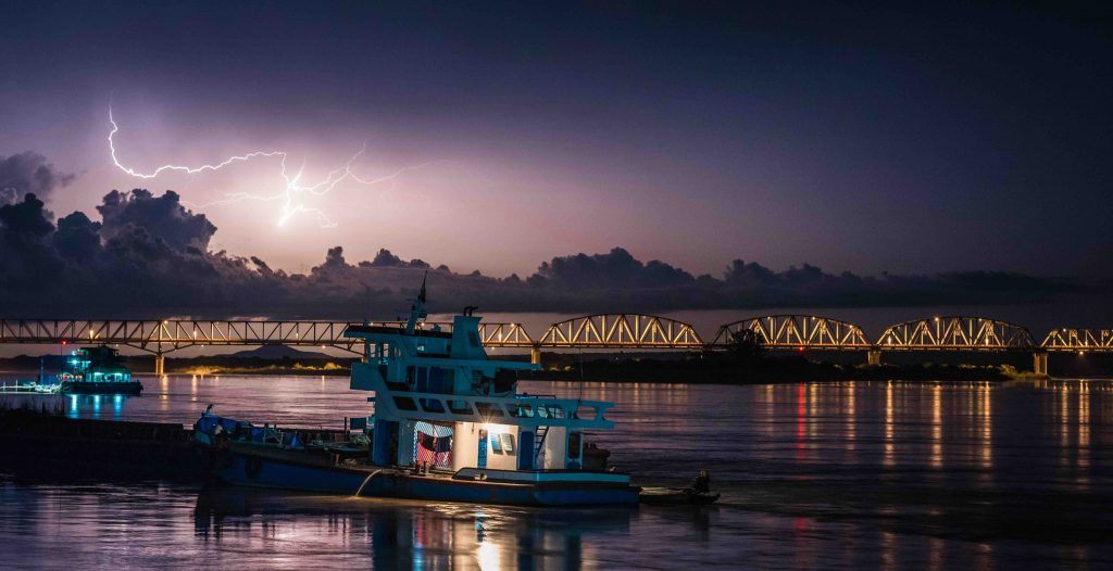 Lightning over bridge with boats in foreground