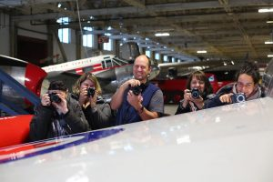 Photography course participants holding cameras in an aircraft hanger during class