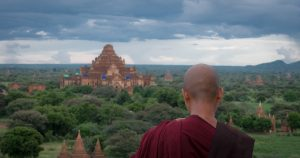 Monk looking out of viewpoint at landscape filled with temples