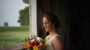 Portrait photo of bride standing at window looking at bouquet of flowers in natural light