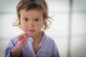 Close up of young toddler girl chewing on a straw