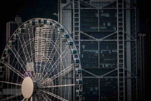 Ferris wheel in front of large high-rise buildings in city