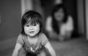 Young toddler girl crawling down hallway with woman in background