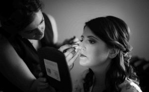 Spotlight effect on portrait of bridesmaid having makeup applied in black and white
