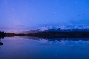 Stars and mountains reflected in lake with glow of city lights on horizon
