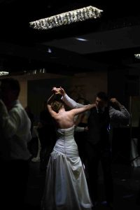 Young bride and groom dancing first dance at wedding with spotlight on bride