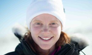 Close up portrait of young woman's face with blue eyes wearing a white hat and black jacket