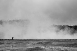 Person standing on boardwalk at Yellowstone National Park in the distance with fog rising in black and white