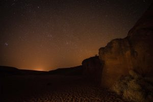 Stars at night in desert with glow of city lights on the horizon