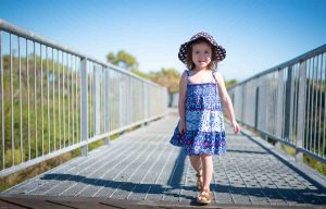 Young girl in blue dress and black and white hat walking along a raised walkway above vegetation