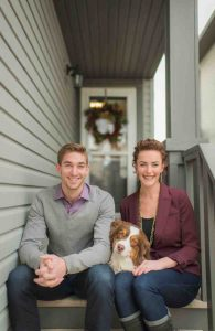 Young couple with dog sitting on front steps of house with Christmas wreath in background