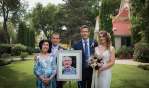 Family formal photo at wedding with bride, groom and grooms family